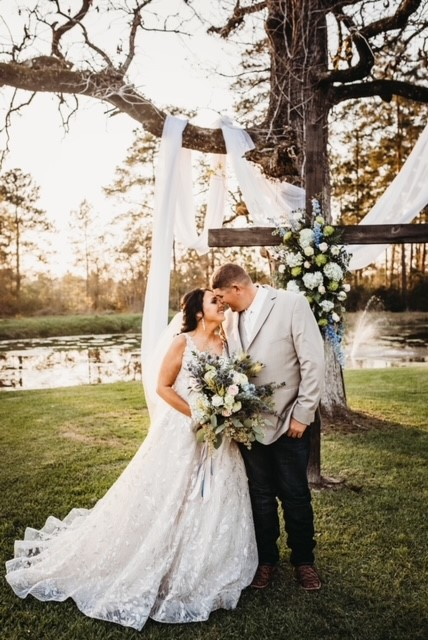 Couple in front of cross at Mansion Lake